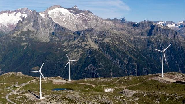 Bild von drei Windrädern auf dem Stöckli in Andermatt, Kanton Uri, im Hintergrund sieht man Berge.