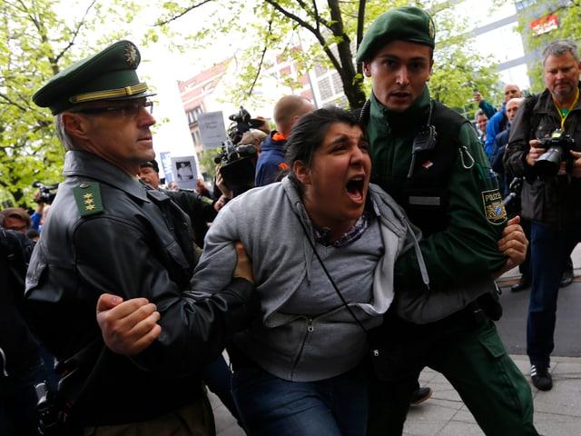 Zwei Polizisten halten eine wütende Demonstrantin fest.