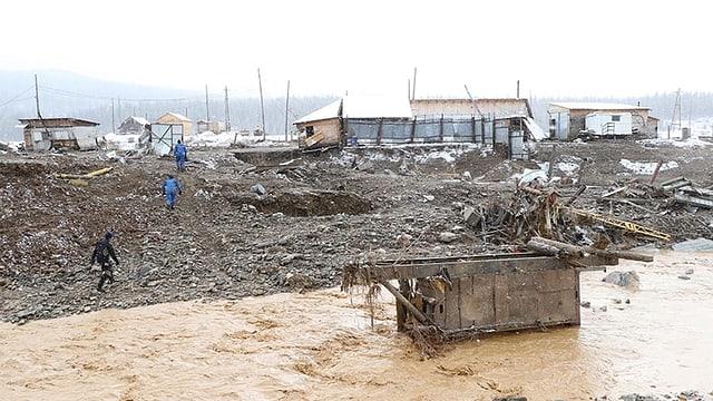 Baracken, teilweise abgerissen, stehen in braunen Wassermassen. Es regnet.
