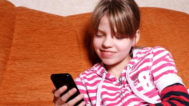 Mädchen sitzt auf dem Sofa und schaut ins Smartphone