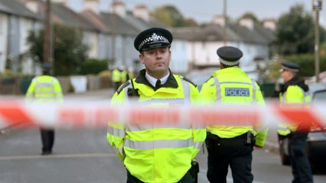 Polizeibeamte hinter einem Absperrband.