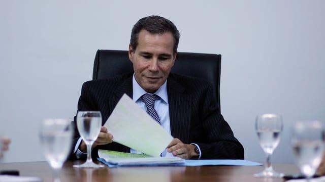Ein Mann im Anzug sitzt an einem Tisch, in seinen Händen hält er Dokumente