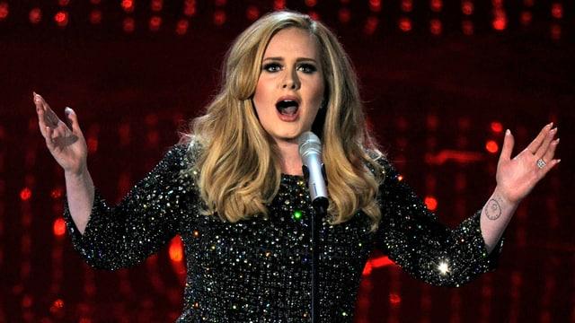 Sängerin Adele mit Miktrofon am singen.