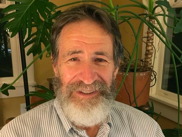 Ein älterer Mann mit Bart sitzt in einem Wohnzimmmer
