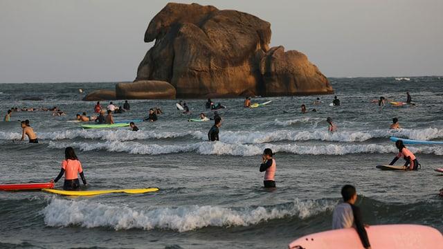 Chinesische Touristen surfen an einem Strand in Hainan.