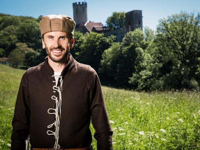 Mann in mittelalterlicher Kleidung auf einer Wiese mit einer Burg im Hintergrund