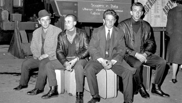 Vier Einwanderer sitzen auf ihren Reisetaschen am Bahnhof.