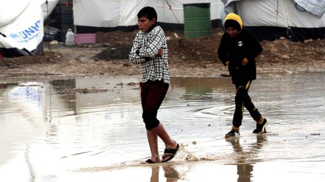 Zwei Knaben waten frierend durch eine riesige Pfütze in einem UNHCR-Flüchtlingslager.