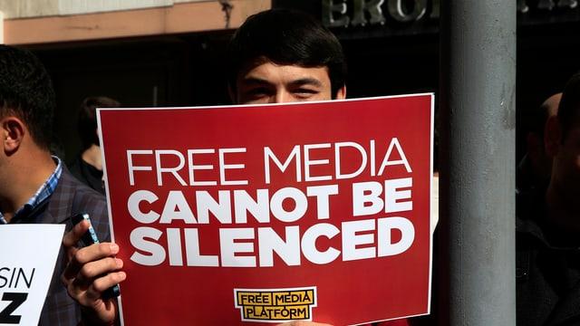 Symbolbild: Ein Mann hält ein Schild hoch, darauf heisst es: Freie Medien können nicht zum Schweigen gebracht werden.