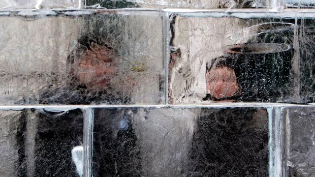 Zwei Menschen hinter einer Eismauer.