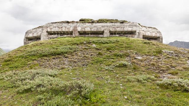 Eine überwachsene Betonfestung auf einem grünen Hügel.