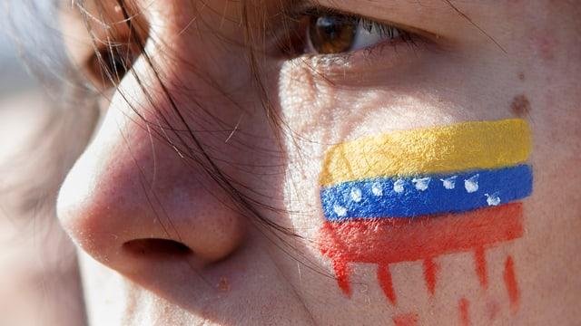 Eine Person mit einer Venezuela-Flagge auf der Wange.