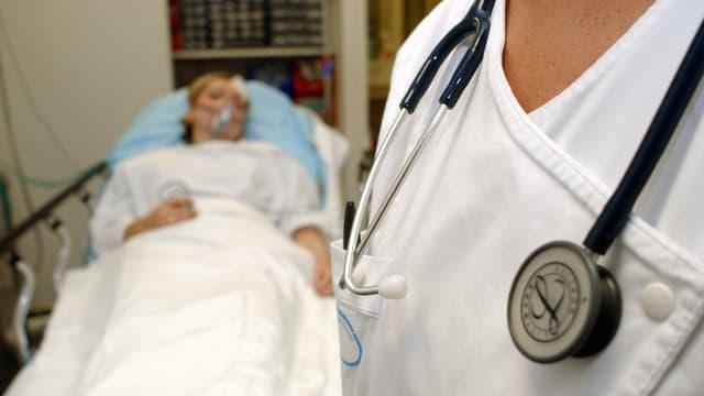 Ein Arzt steht am Bett einer Patientin mit Sauerstoffmaske