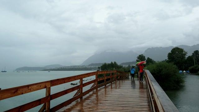 Regenwolken hängen über dem See. Auf dem Steg Leute mit Regenschirm.