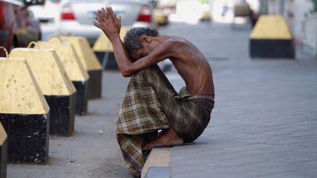 Ein völlig abgemagerter Mann mit einem um die Hüfte geschlungenen Tuch sitzt auf einem Trottoir und hebt die Hände.