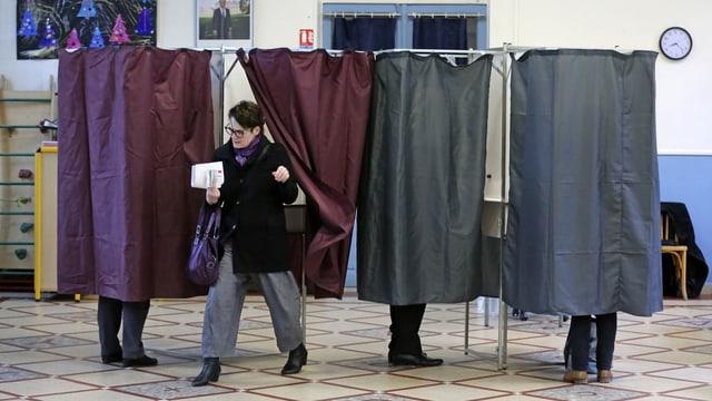 Vier Vorhänge als Wahlkabine, dahinter sieht man Füsse. Eine Frau kommt grade raus.