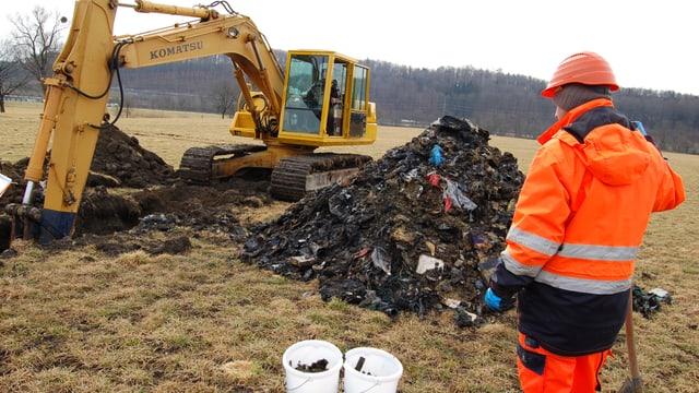 Wiese, Bagger gräbt grusigen Güsel aus dem Boden aus, ein Bauarbeiter im orangen Gwändli steht daneben.