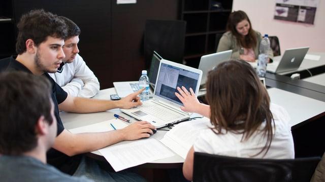 Junge Erwachsene sitzen um einen Schreibtisch und arbeiten mit Computern und Büchern