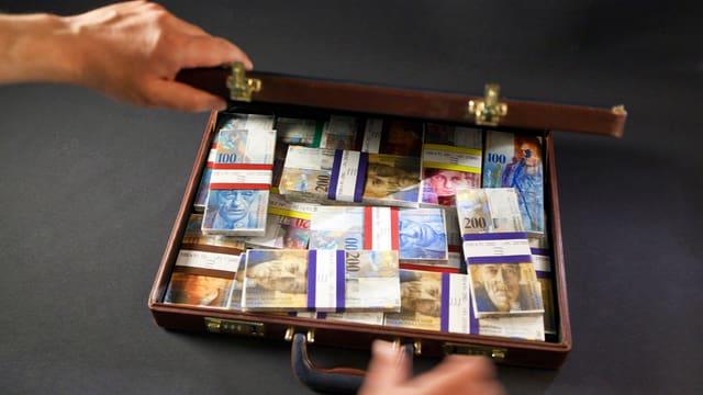 Ein geöffneter Aktenkoffer gefüllt mit Geldscheinen. Schweizer Geld.