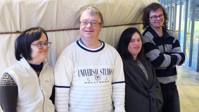 Vier lachende Menschen stehen vor einer Stoffwand.