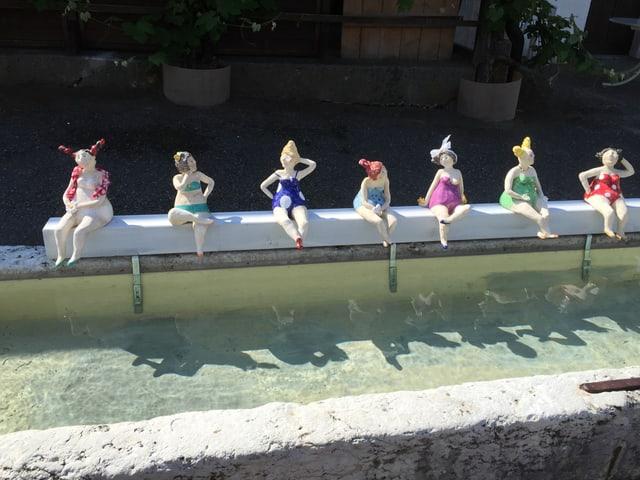 Frauenfiguren stehen auf dem Brunnenrand.