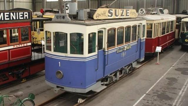 Ein altes, blau-weisses Tram steht in einer Halle neben anderen Trams.