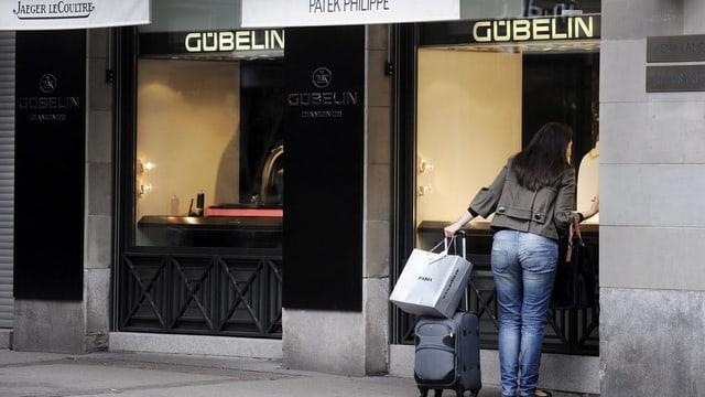 Eine Frau schaut in ein Schaufenster eines Schmuck-und Uhrengeschäftes in Zürich.