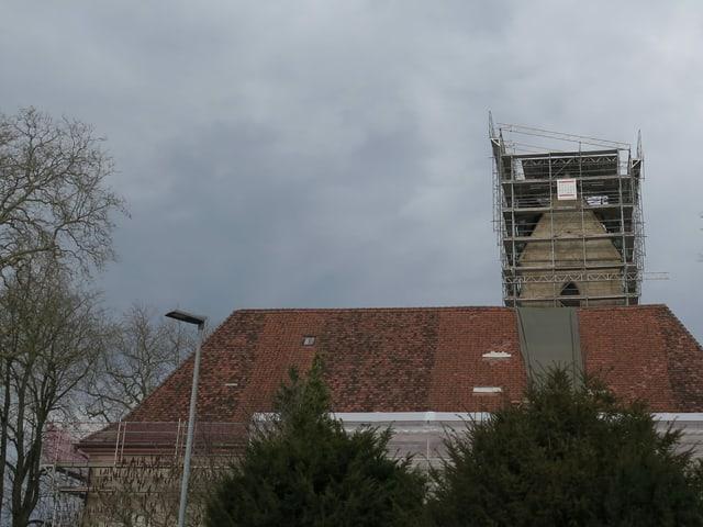 Kirchturm im Gerüst, hinter einem grossen Hausdach.