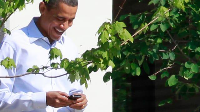 US-Präsident Barack Obama beschäftigt sich mit seinem Handy.