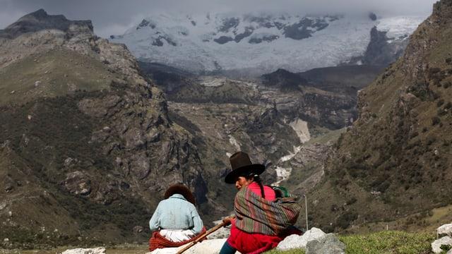 Zwei Frauen sitzen auf einem Berg mit Blick ins Tal, im Hintergrund der Hualcan-Gletscher.