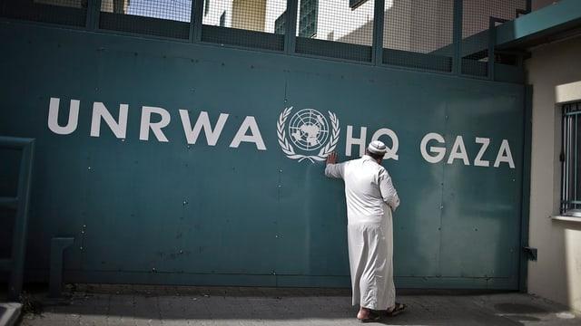 Ein Mann lehnt an eine Wand, auf der as Logo von UNRWA zu sehen ist.