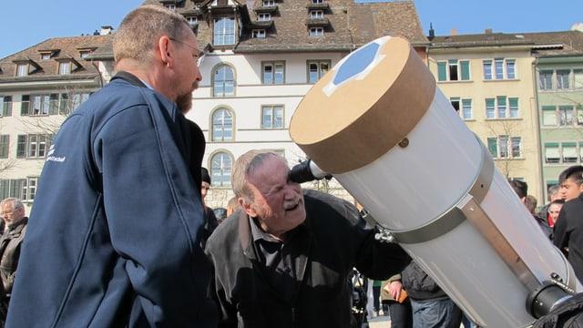 Ein Mann schaut durch ein Teleskop