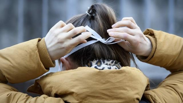 Eine Frau bindet sich einem Mundschutz um.