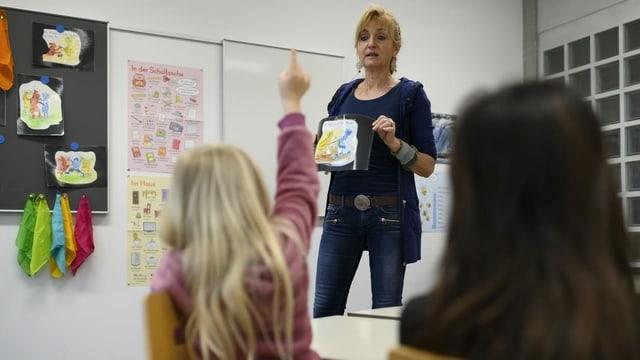 Eine Lehrerin erklärt etwas vor zwei Schülerinnen, eine davon streckt die Hand in die Luft.