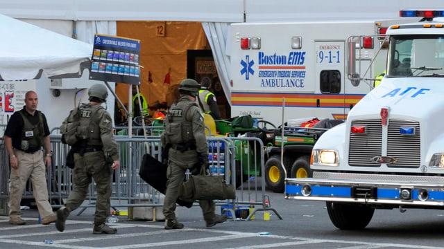 Uniformierte FBI-Beamte mit Taschen, im Hintergrund Ambulanzfahrzeuge