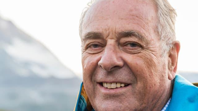 Kopf von Alt Bundesrat Adolf Ogi, er lächelt in Kamera, im Hintergrund eine Bergflanke.