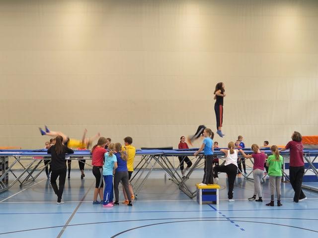 Kinder hüpfen auf Trampolin in Turnhalle