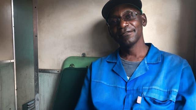 Ein mittelalter Mann sitzt auf einem Zugsitz und trägt einen blauen Overall.