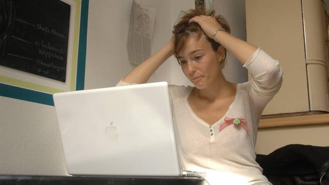 Eine Frau sitzt vor dem Computer und rauft sich die Haare