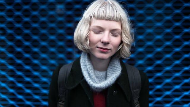 Eine blonde junge Frau vor einem Blauen Hintergrund. Sie hat die Augen geschlossen.