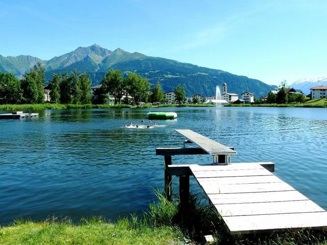 Bergsee mit Schwimmsteg vor blauem Himmel