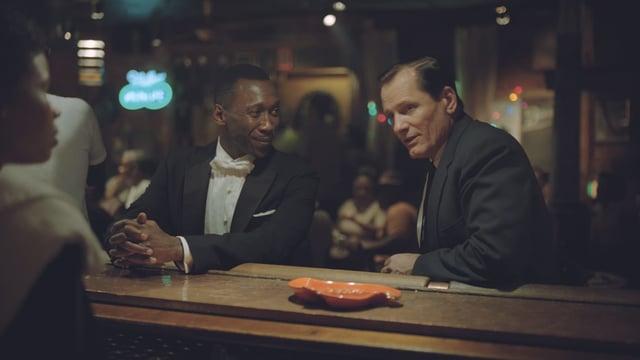 Viggo Mortensen und Mahershala Ali an einer Bar sitzend