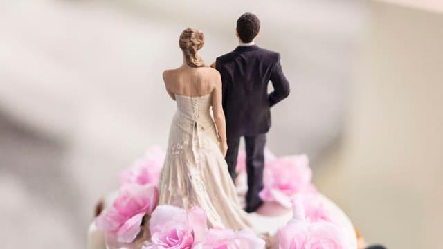 Die Spitze einer Hochzeitstorte mit Braut und Bräutigam aus Zucker