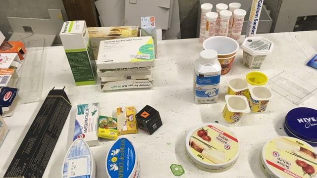 leere Jogurtbecher, Käseschachteln und Verpackungen auf deinem Tisch