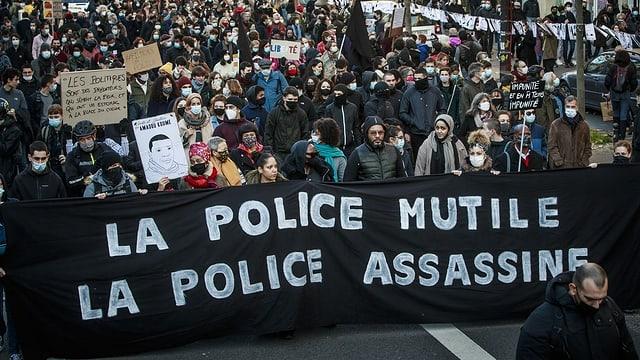 Demonstranten tragen ein Banner. Darauf steht auf Französische: Die Polizei mutiliert, die Polizei mordet.