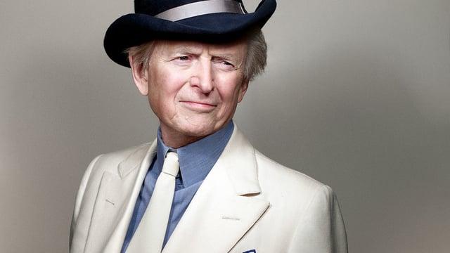 Nahaufnahme eines älteren Mannes mit Hut und weissem Anzug.