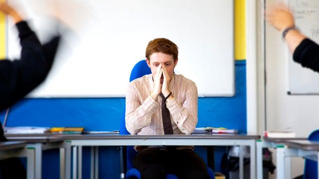 Ein verzweifelter Lehrer sitzt an einem Tisch.