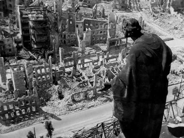 Skulptur über zerstörten Häusern.