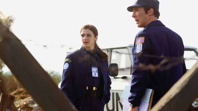 Eine Polizistin und ein Polizist in Uniform stehen vor einem Auto.