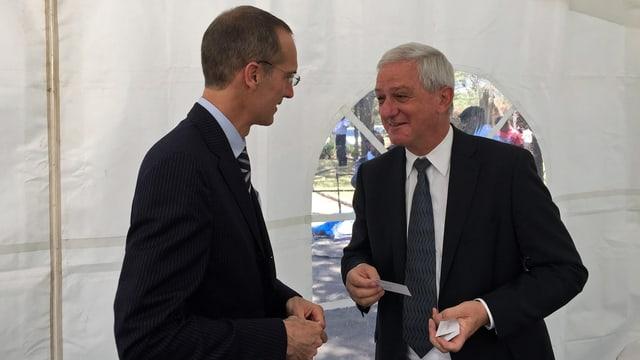 Zwei Männer sprechen in einem weissen Zelt miteinander.